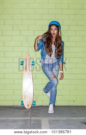 Beautiful Long-haired Woman With A Wooden Longboard Near A Green Brick Wall