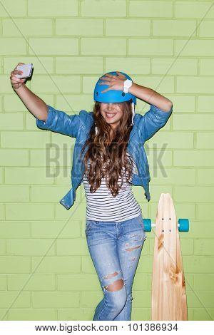 Beautiful Long-haired Girl With A Smartphone Near A Green Brick Wall