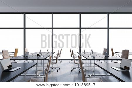 Workplaces In A Modern Panoramic Office, Copy Space In The Windows. Open Space. White Tables And Bro