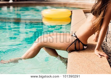 Beautiful Athletic Young Girl In A Sexual Striped Bikini Is Sitting On The Edge Dangling Her Feet In