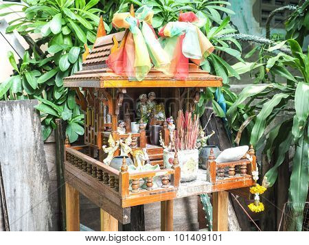 Brown Spirit House In Thailand With Flowers In A Vase