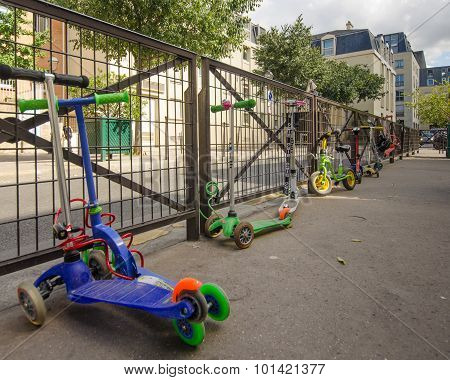 Children's scooters are locked to the fence of the school yard in Paris
