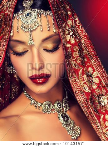 Beautiful Indian woman portrait In traditional jewelry and red saree