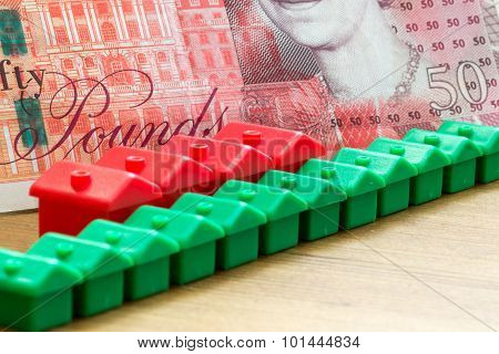 Green Red Plastic House Models In A Diagonal Row With British Bank Note