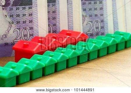 Green Red Plastic House Models In A Diagonal Row With Bank Notes
