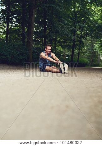 Man Sitting On The Ground And Reaching His Toes