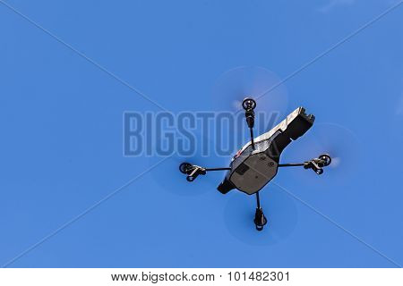 a small spy quad copter drone flying over a clear blue sky poster