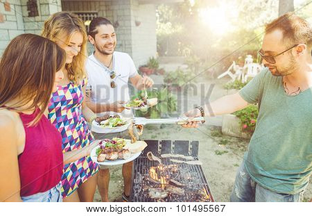 Group Of Friends Making Barbecue In The Garden Backyard
