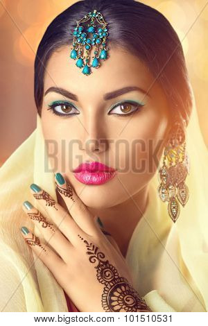 Beauty Indian woman portrait. Brunette Hindu model girl with brown eyes, mehendi tattoo on her hand and national Indian jewels looking in camera. Indian girl in sari. Traditions