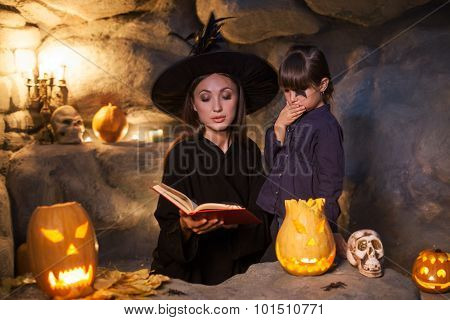 Beautiful evil witch is showing the kid witchcraft