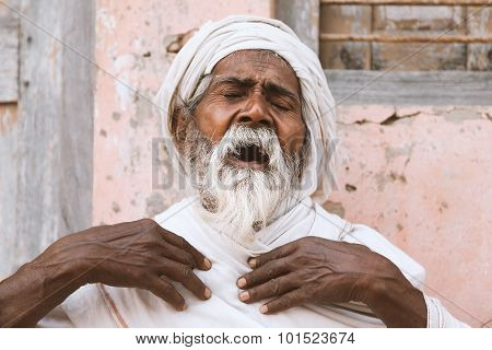 Old indian sadhu speaking scriptures.