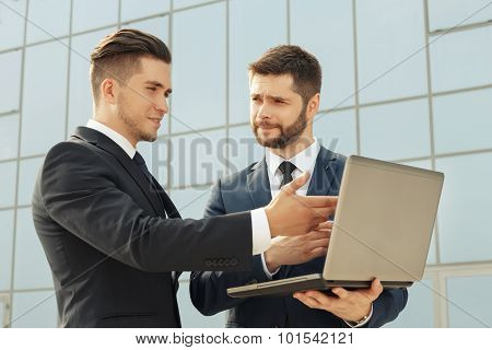 Businessmen using laptop while having a meeting