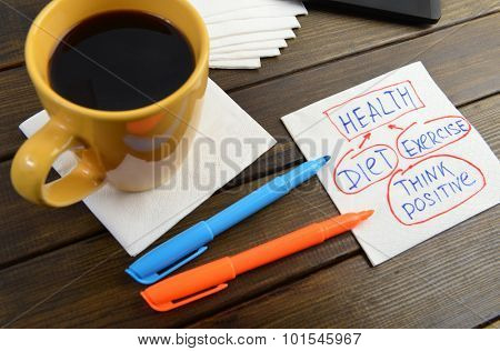 health analise diet exercise think positive -  handwriting on a napkin with a cup of coffee and phone