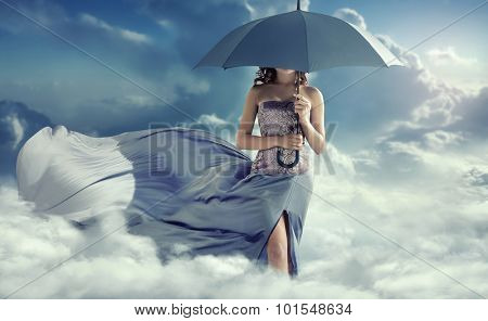 Young lady with an umbrella walking in the clouds