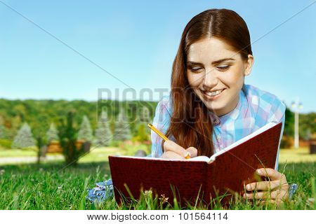 Beautiful girl in park with her diary