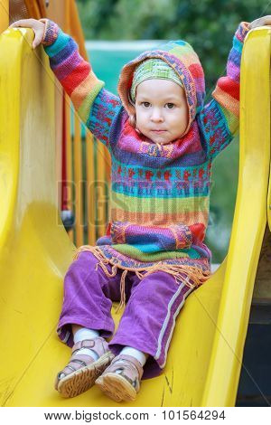 Toddler girl wearing woolen knitted sweater with hood is sitting on plastic playground slide