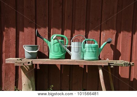 Bucket And Three Watering Pots With Red Wooden Wall Background