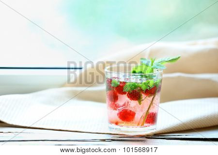 Glass of cold refreshing summer drink with berries and ice cubes on table close up poster