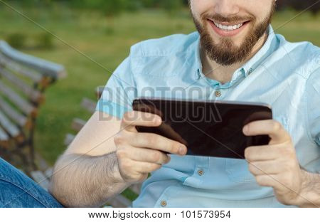 Smiling young man texting on the tablet
