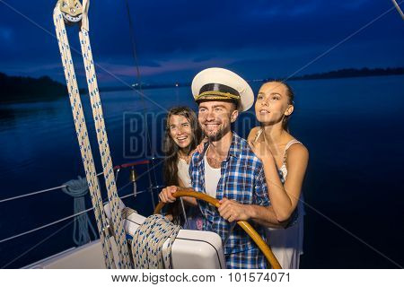 Captain with girls on the yacht. Night cruise on the yacht. Friends traveling by yacht on the river. Holiday on a yacht. poster