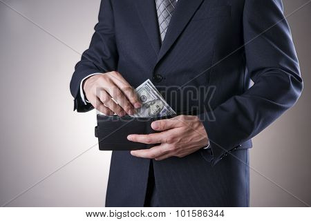 Businessman With Money In Studio On A Gray Background