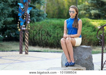 The Girl In Sun Glasses And With Long To Hair Sits On A Stone.