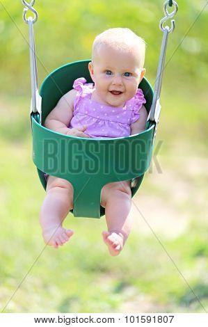 Happy Baby Girl Swinging At Playground