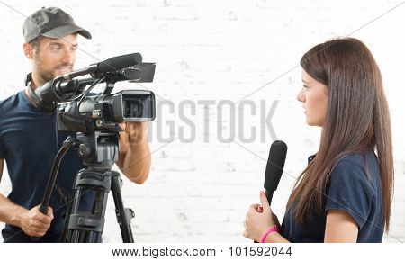 A Young Woman Journalist With A Microphone And A Cameraman