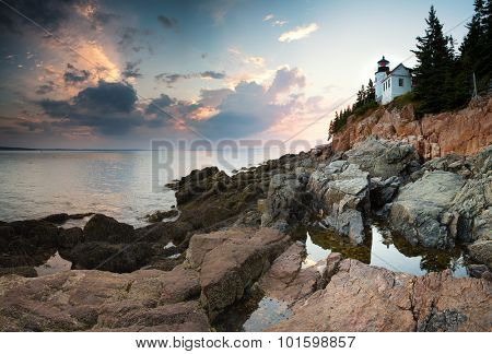 Sunset at Bass Harbor Lighthouse, with the light reflected ed in the rock pools, Mount Desert Island, Maine, USA