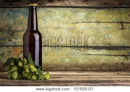 One Bottle Of Beer With Bunch Of Hops On Wood Background