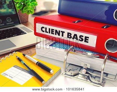 Client Base - Red Office Folder on Background of Working Table with Stationery, Laptop and Reports. Business Concept on Blurred Background. Toned Image. poster