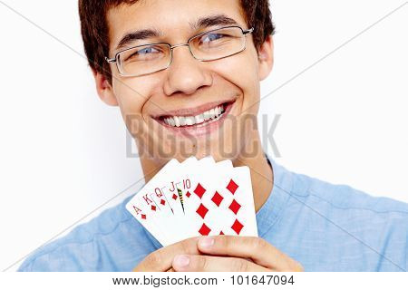 Close up portrait of young hispanic man wearing jeans shirt and glasses holding Royal Flush (highest-ranking standard poker hand) in his hand and smiling against white wall - gambling winnings concept