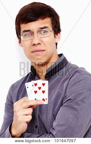 Close up portrait of young disappointed hispanic man wearing grey shirt holding 2-7 (worst standard poker starting hand) in his hand against white wall - gambling failing concept