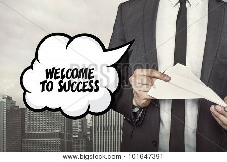 Welcome to success text on speech bubble with businessman holding paper plane in hand