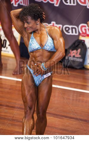 Female Bodybuilder In Abdominals And Thighs Pose And Blue Bikini