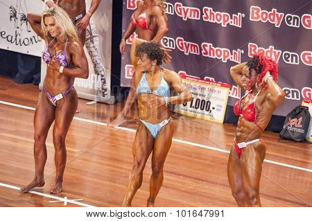 Three Female Bodybuilders In Abdominals And Thighs Pose In Lineup