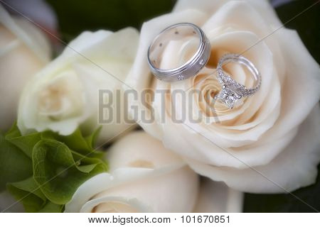 Closeup of wedding rings on a rose bouquet