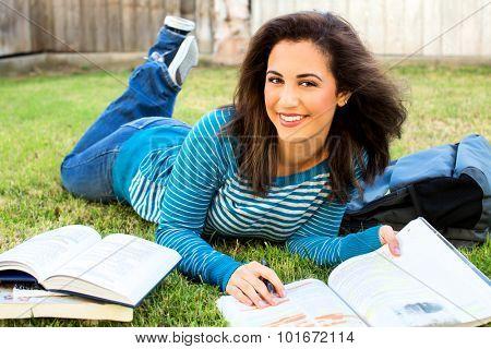 Young ethnic woman doing school work outside