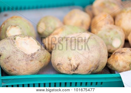 sale, harvest, food, vegetables and agriculture concept - close up of swede or turnip in plastic box at street market