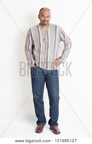 Full length confident mature casual Indian man standing on plain background with shadow.