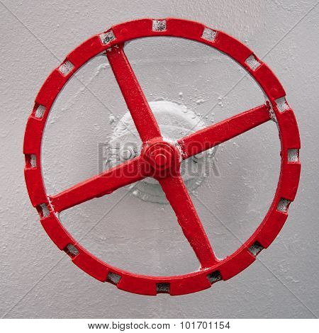 old red hand wheel on the wall of tank