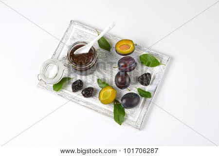 plum jam, fresh and dried plums on wooden cutting board poster