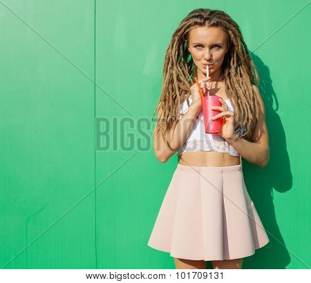 Beautiful sexy blonde with dreads and blue eyes drinking beverage through a straw on a hot summer da