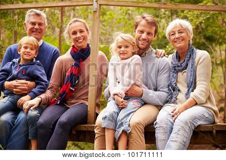 Multi-generation family portrait on a bridge in a forest