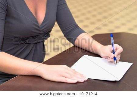 Women's Hands With A Pen Filling The Form On The Desk In The Office
