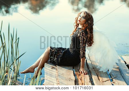 Girl With Wings Of An Angel Sitting Near A River.