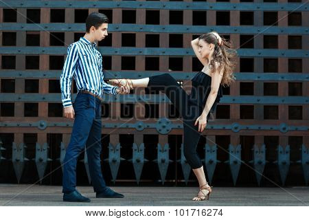 Man holding a girl's leg, they dance the dance.