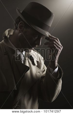 Detective adjusting his hat standing in the dark film noir poster