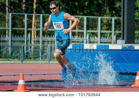 male athlete running the steeplechase