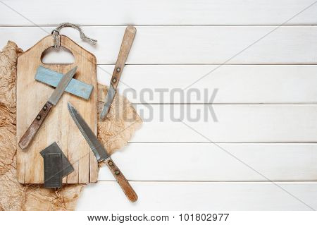 Knifes And Grindstone On The White Wooden Table